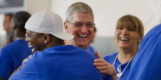 Tim Cook, chief executive officer of Apple Inc., center, hugs an employee during the sales launch for the iPhone 6 and iPhone