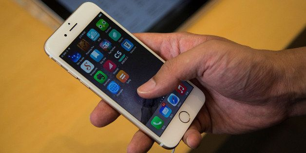 HONG KONG - SEPTEMBER 19:  Customer looks at the new iPhones on display at the launch of the new Apple iPhone 6 and iphone 6