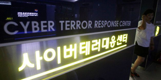 FILE - In this July 16, 2013 file photo, a woman walks by a sign at Cyber Terror Response Center of National Police Agency in