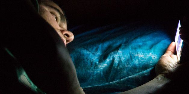 Man laying on bed at late night in a dark room checking his smartphone. Internet