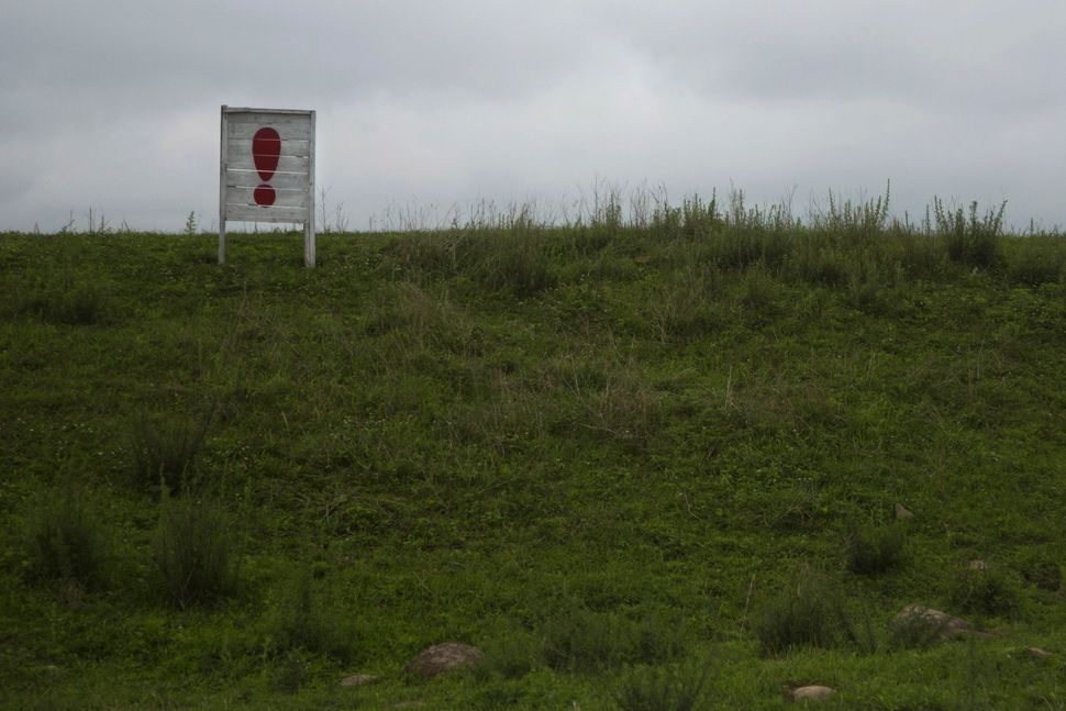 In this June 20, 2014 photo, an exclamation point punctuates a long propaganda slogan in a field in North Korea's North Hamgy