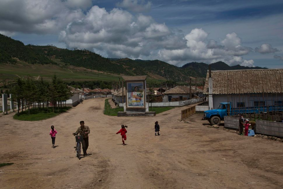 In this June 19, 2014 photo, residents of a small roadside town walk towards the main road in North Korea's North Hamgyong. (