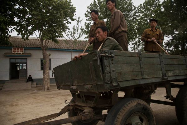 In this Monday, June 16, 2014 photo, North Korean men ride in a farmer's wagon in North Korea's South Hamgyong province. (AP