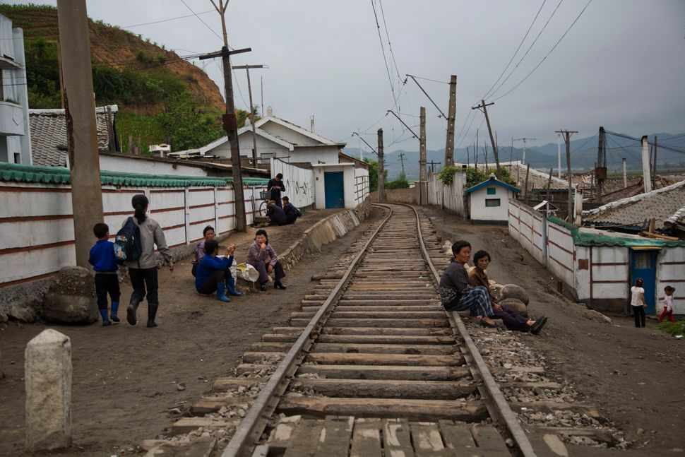 In this June 20, 2014 photo, North Korean people rest next to the railroad tracks in a town in North Korea's North Hamgyong p