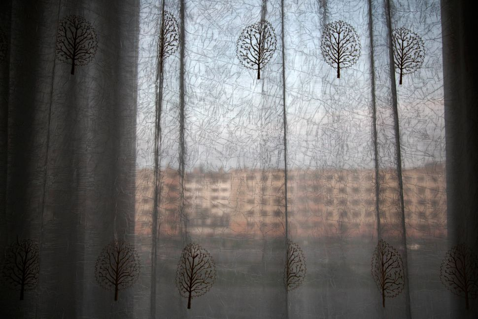 In this June 15, 2014 photo, an apartment block stands behind hotel room curtains on the main street in Hamhung, North Korea.