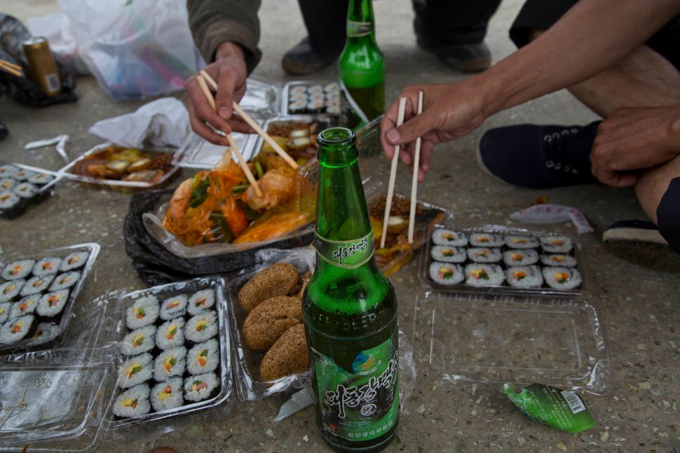 In this June 16, 2014 photo, North Korean men share a picnic lunch and North Korean-brewed and bottled Taedonggang beer along