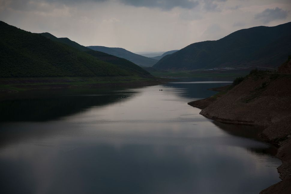 In this June 16, 2014 photo, a fishing boat crosses the Samsu reservoir near the town of Samsu in North Korea's Ryanggang pro