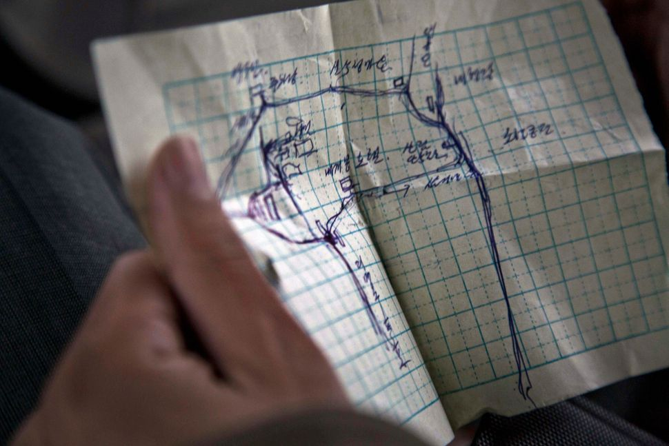 In this June 17, 2014 photo, a North Korean man holds a hand drawn map of the areas around Mt. Paektu as he and colleagues dr