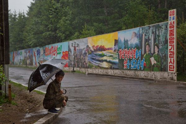 In this June 17, 2014 photo, a North Korean man takes shelter in the rain next to long propaganda billboards in the town of S