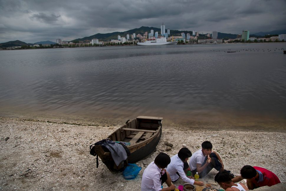 In this June 21, 2014 photo, a group of young North Koreans enjoys a picnic on the beach in Wonsan, North Korea. (AP Photo/Da