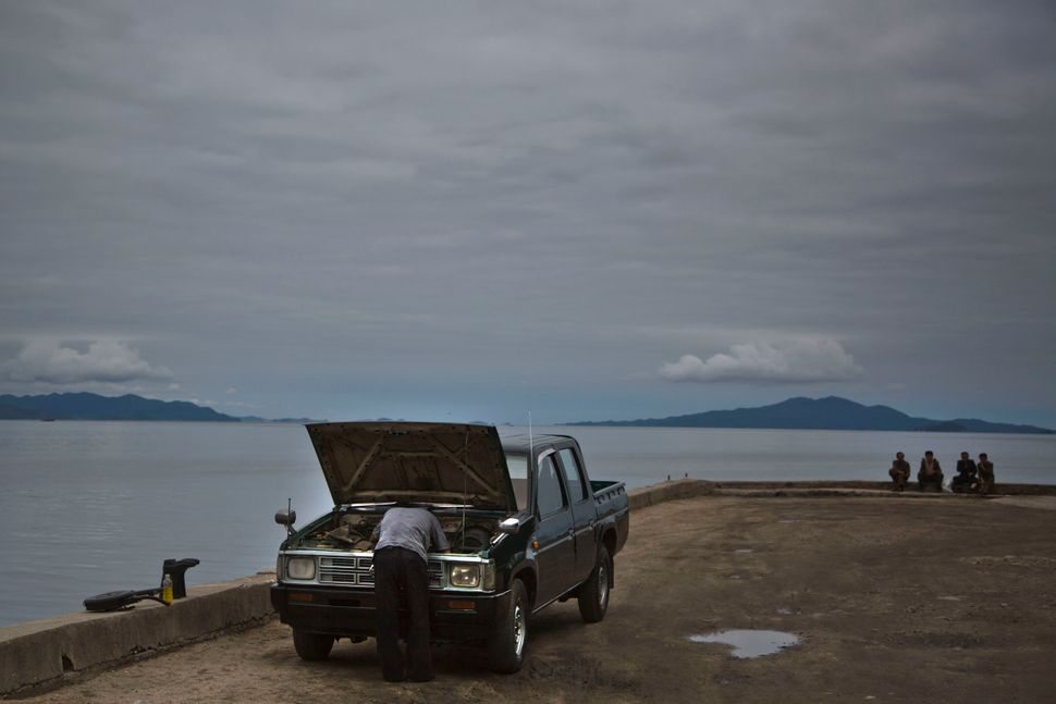 In this June 21, 2014 photo, a man works on his car as others sit next to the sea Wonsan, North Korea.  (AP Photo/David Gutte