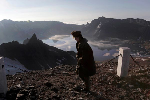 In this Wednesday, June 18, 2014 photo, a North Korean woman walks on the peak of Mt. Paektu in North Korea's Ryanggang provi