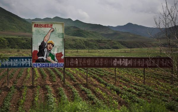 In this Monday, June 16, 2014 photo, a propaganda billboard stands in a field south of Samsu, in North Korea's Ryanggang prov