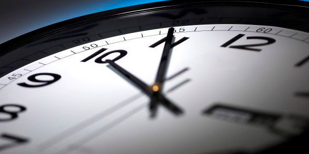 minute hour second hand timeclock late hour black and white clock on a dark blue background (Photo by:...