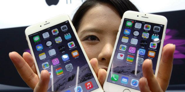 FILE - In this Sept. 19, 2014 file photo, a customer shows off the new Apple iPhone 6 and 6 Plus at a store in Tokyo. Apple I