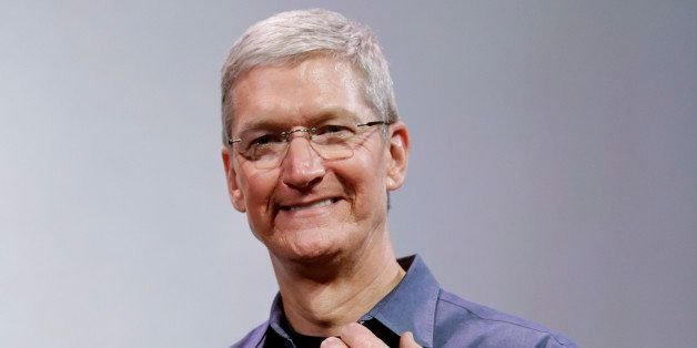 Apple CEO Tim Cook, holding an IPhone 6 Plus, discusses the new Apple Watch and iPhone 6s on Tuesday, Sept. 9, 2014, in Cuper