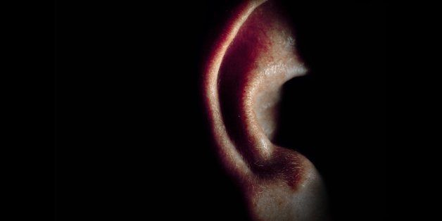 Close up of man's ear, half illuminated, in dark room.