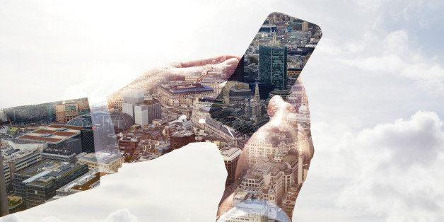 Double exposure of a business man using a smart phone with a view of the city of London and the sky.