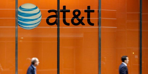 In this Tuesday, Oct. 21, 2014 photo, people pass an AT&T store on New York's Madison Avenue. AT&T says it will buy M