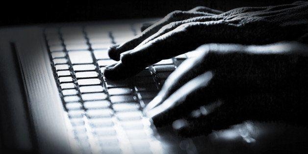 Concept photo in high contrast black and white of hacker's fingers on keyboard