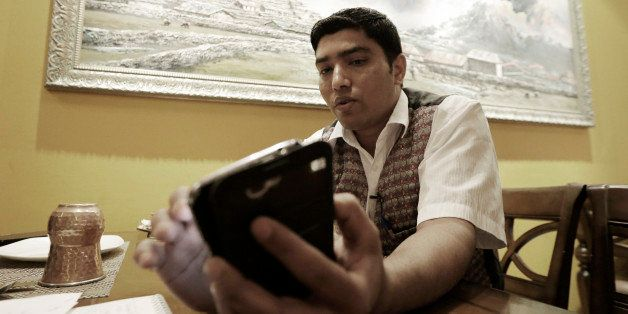 Bigyan Bhandari, a 28-year-old Nepalese who works at a Nepalese restaurant run by K.P. Sitoula, uses his smartphone to call h