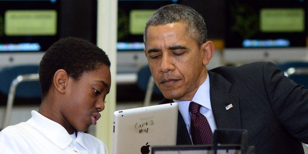 A student shows US President Barack Obama how he is working to creat an ebook with an iPad in a classroom at Buck Lodge Middl