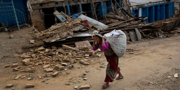 A Nepalese woman carrying belongings walks past a damaged house in Chautara, Nepal, Wednesday, May 13, 2015. The condition of