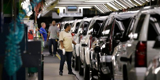 FILE - In this May 13, 2014 file photo, an auto worker inspects finished SUVs coming off the assembly line at the General Mot