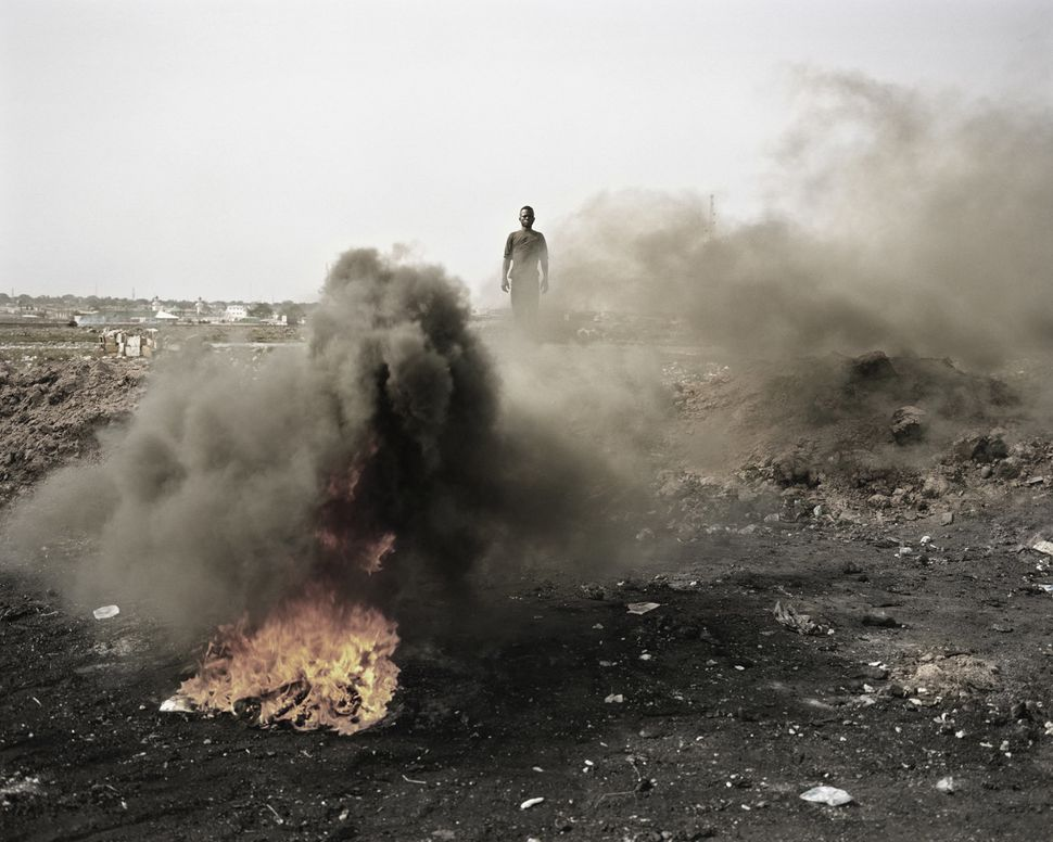 Agbobloshie, Accra, Ghana.  A man stands in the midst of smoke, fire and residual parts of electronic equipment as he burns i
