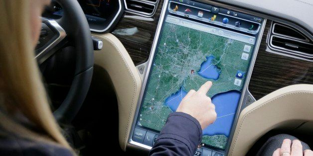 In this Tuesday, April 7, 2015 photo, Alexis Georgeson of Tesla Motors shows off the navigation screen during test drive of t