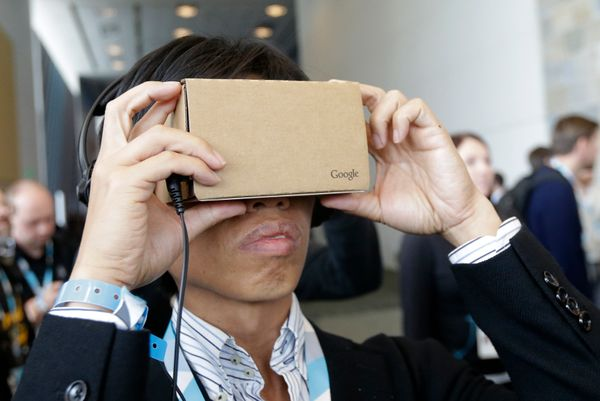 A man looks at Google Cardboard during Google I/O 2015 in San Francisco, Thursday, May 28, 2015. (AP Photo/Jeff Chiu)
