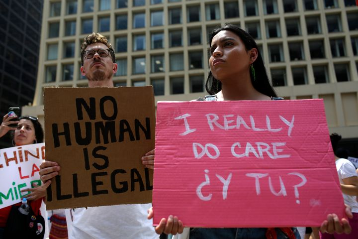 """A demonstrator holds a sign reading """"No Human Is Illegal"""" during a protest in Chicago in June against Immigration and Customs Enforcement (ICE) and the Trump administration's immigration policies."""