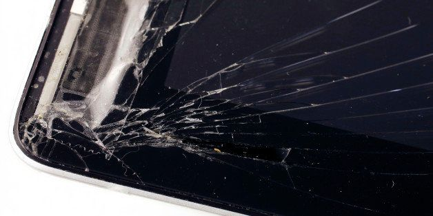An iPad has a cracked screen in this studio photo, Friday, Dec. 6, 2013 in New York. Many device protection plans can be star