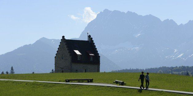 Hikers walk past a building of hotel Kranzbach in the Alp mountains in Elmau near Garmisch-Partenkirchen, southern Germany, o