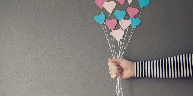 A hand holding the strings of a bunch of blue & pink paper hearts like they are balloons.