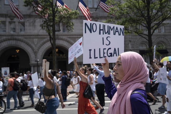 """A demonstrator in Washington, D.C., holds a sign reading """"No Human Is Illegal"""" while marching past the Trump International Hotel during a protest against the president's immigration policies."""