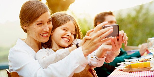 Happy mother and daughter taking selfie through smart phone at outdoor table in yard