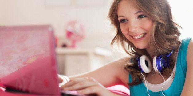 Teenage girl typing on laptop