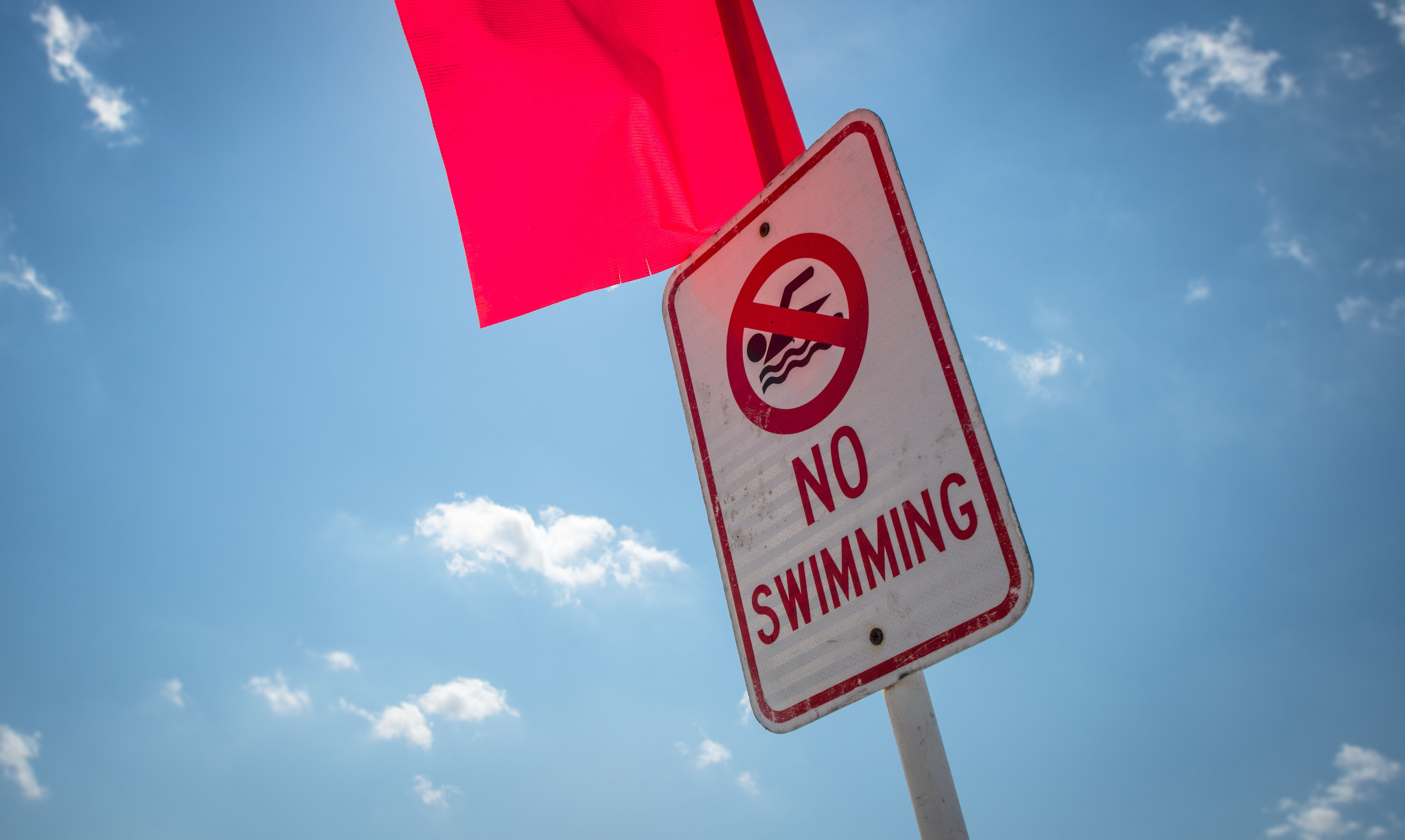 A 'no swimming' sign and a bright red flag warn potential swimmers of danger.