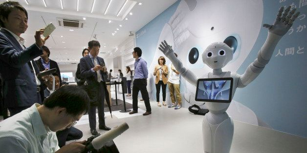 FILE - In this June 6, 2014 file photo, journalists surround humanoid robot Pepper on display at SoftBank Mobile shop in Toky