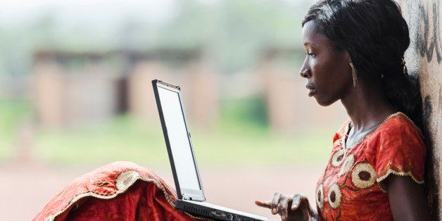 Street Shot of an African Ethnicity young woman working on business holding her technology item computer in a university in B