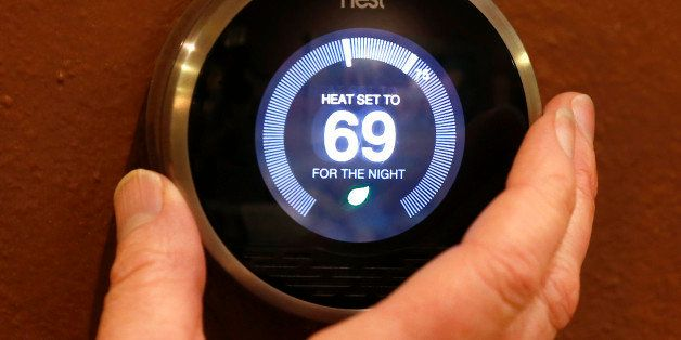 PROVO, UT - JANUARY 16: In this photo illustration, a Nest thermostat is being adjusted in a home on January 16, 2014 in Prov
