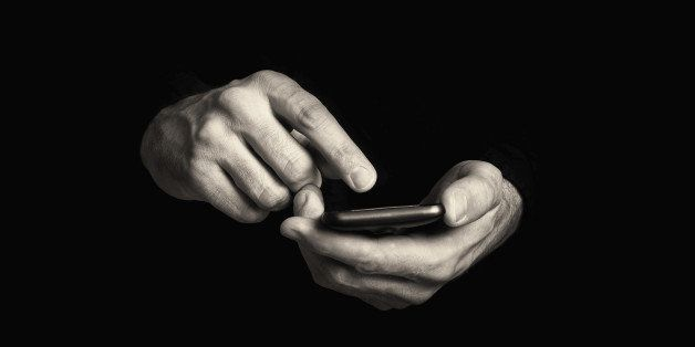 Man typing text message on his smartphone, focus on hands and the phone device.
