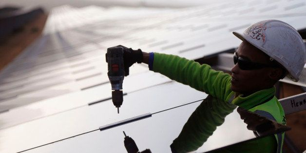 A worker installs a solar panel at a photovoltaic solar park situated on the outskirts of the coastal town of Lamberts Bay, S