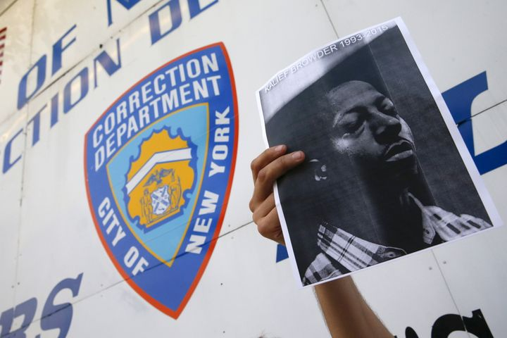 A demonstrator holds a photo of Kalief Browder during a vigil outside the entrance to the Rikers Island correctional facility