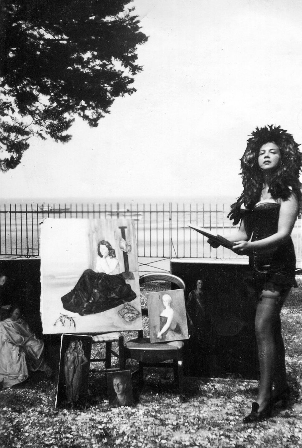 Leonor Fini painting in a feather headdress.