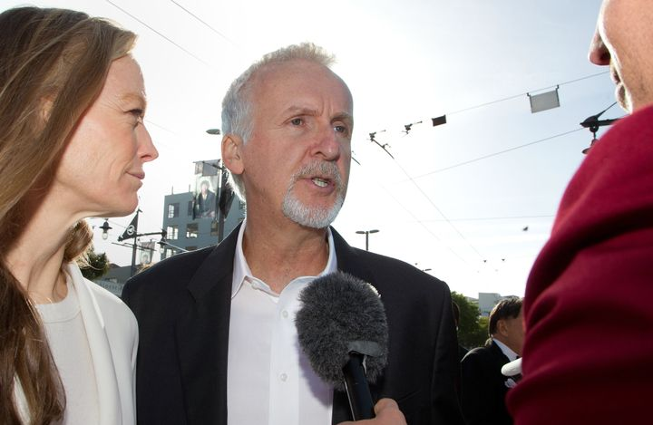 Director James Cameron (C) and Suzy Amis (L) speak to the media upon their arrival at the world premiere of 'The Hobbit' movi