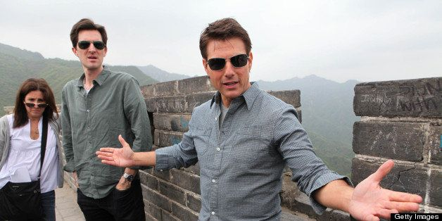 American actor and producer Tom Cruise (R) gestures as he visits the Mutianyu Great Wall in Beijing on May 9, 2013. His new movie 'Oblivion' would be released in China on May 10, state media reported. CHINA OUT AFP PHOTO (Photo credit should read STR/AFP/Getty Images)