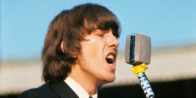 British singer, composer and musician George Harrison playing guitar and singing during the concert of British band The Beatl