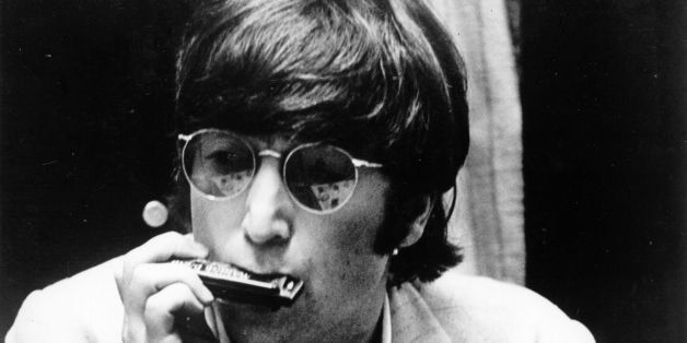 22nd June 1966:  Beatles singer, songwriter and guitarist John Lennon (1940 - 1980) plays the harmonica, his guitar rested on
